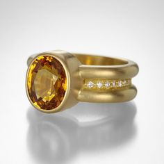 From their signature collection, this Reinstein/Ross ring exemplifies the luxury, sophisticated design, and unparalleled quality that is the hallmark of their jewelry. Featuring a fiery oval orange sapphire, on a 20k peach gold and diamond 'Shimmer Band,' this design is clearly contemporary, but inspired by time honored goldsmithing techniques. A true heirloom in the making! Orange sapphire = 4.20cts.Size 5.75.