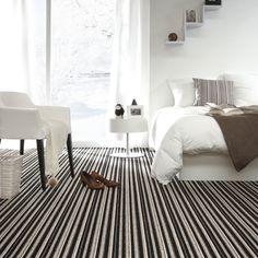 Een moderne slaapkamer met strak gestreept tapijt in natuurlijke tinten. Alles is mogelijk met tapijt!