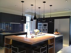 A sleek and modern kitchen, featuring pendant lighting that hangs close to the island, illuminating a very controlled space. The black cabinetry is accented by chrome details and the wood grain eat-in extension.