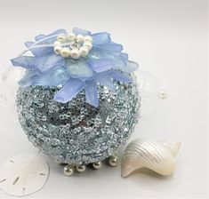 """Beach Christmas ornament in beautiful blue ice and sea glass! Coastal, nautical,  and a fabulous beachy soft blue, this ball ornament is a sure hit for a beachy decor. It's totally covered in pretty ice, then topped with our gorgeous """"blue"""" sea glass in plus pretty crowning pearls.  The shade of icy light blue is perfect for all coastal decors, and the ice and the sea glass give it a lot of bling!  4"""" acetate ball."""