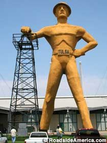 """The Golden Driller - Long-ago Tulsa sat atop the world's largest known pool of oil. Drilling derricks were everywhere and the city called itself """"Oil Capital of the World."""" To celebrate this good fortune, a giant roustabout was built on the Tulsa Fairgrounds in 1953. Dubbed """"The Golden Driller,"""" he resembled an oversized brass statuette, with a big grin on his face, his tin hat tipped back in a rakish skew, and his gloved right hand raised in a kind of limp-wristed OK sign."""
