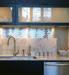 Blue framed kitchen cabinets look sophisticated above a shining black splash