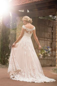 D2327 Off-the-shoulder Boho Wedding Gown by Essense of Australia. The casual boho wedding dress by Essense of Australia is simply a dream come true! Trend-worthy lace off-the-shoulder sleeves pair with a deep sweetheart neckline that lies just under the sheer lace overlay. #weddinggowns