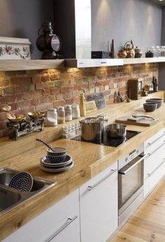 Rustic brick backsplash: Rustic and Full of Charm. i love the butcher block counter with the lip for odds and ends containers