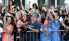 Grandma enjoys the moment while the whole crowd is on their phones