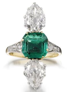 An emerald and diamond ring, first quarter of the 20th century  Set to the centre with a step-cut emerald, between two vertically aligned pear-shaped diamonds, weighing 1.59 and 1.51 carats, the shoulders decorated with graduating trios of old brilliant-cut diamonds, numbered