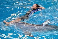 """Her job as an associate marine mammal trainer can be demanding, but Mallory Mara makes time to relax with her dolphin buddies at Clearwater Marine Aquarium in Florida, where the Elk Grove Village native works with Winter and Hope, the stars of the """"Dolphin Tale 2"""" movie."""
