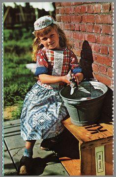 Marker jongetje poseert in dracht voor onder de zes jaar met tobbe. Jongetjes worden gekleed en gekapt als meisjes tot ze ca. vijf à zes jaar oud zijn. Aan het geruite borststuk kan men zien dat hij een jongen is. 1960-1966 #NoordHolland #Marken