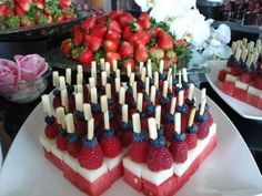Attractive fruit display - watermelon, honeydew, rasberry and blueberry fruit skewers.