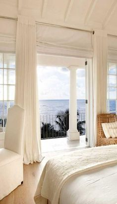 A white beach house, with perfectly breezy curtains, a white covered chair, a wooden chair with a white pillow, and an amazing view!