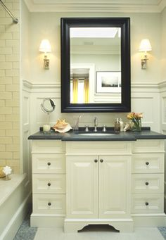 Black ivory bathroom colors. Ivory subway tiles, ivory bathroom cabinet vanity, black corian countertops, chrome sconces, gray ivory marble floors, ivory wainscoting, ivory crown molding and ivory porcelain tub.