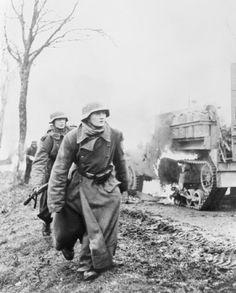 The Battle of the Bulge 16 December 1944 - 28 January 1945: German infantry advancing during the Battle of the Bulge; two soldiers pass a burning US Army vehicle. The soldier in the foreground is a teenager. His comrade following appears to be much older. By the end of 1944, German manpower was in desperate shortage.