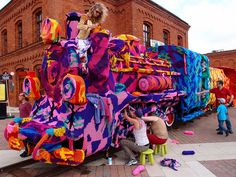 Although currently living in the United States, crochet artist Olek recently returned to her native country of Poland for an epic project. Over the course of two straight (and rainy) days, Olek and her team of four assistants 'yarn bombed' an entire locomotive with two freight cars in tow. Olek had already crocheted many of the panels beforehand but they still had to be assembled to cover the train.