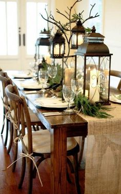 Winter tablescape, with neutrals, lanterns, candles, greenery, pinecones and simple white place settings