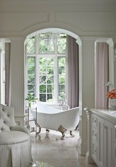 All white bathroom with claw foot tub and the lightest lavender drapes to add a hint of color.