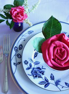 Pink napkin folded to look like a rose. Love this idea!