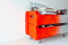 Caixote branco e laranja luminoso com rodízios.