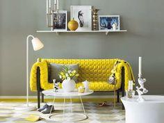 divano giallo con contrasto parete grigia