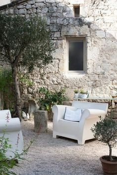 Olive trees, ancient brickwork wall, gravel & ultra modern plastic furniture - awesome old new mix