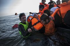 A Syrian refugee is helped by volunteers to leave a sinking dinghy at a beach on the southeastern island of Lesbos, Sunday, Feb. (AP Photo/Manu Brabo)