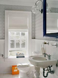 Wainscoting in lower half of bathroom, wallpaper on upper half.