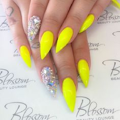 Matte yellow nail art design on long nails. The matte finish on the nails is then contrasted by the single bedazzled design filled with embellishments that naturally stand out from the rest.
