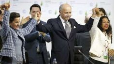 French Foreign Minister Laurent Fabius (centre) and other delegates react to the climate deal in Paris