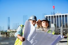 Stock Photo : Architects discussing over blueprint at site
