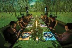 """Diners at Ultraviolet during a """"picnic,"""" with an AstroTurf-covered table and projections of an early-spring meadow on the walls."""
