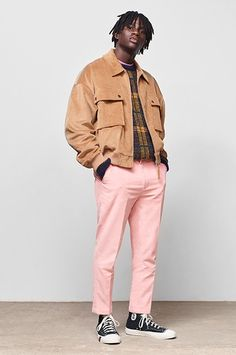 ASOS model wearing a tan corduroy jacket, gold jumper, pink trousers and black Converse trainers | ASOS Style Feed