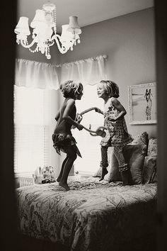 Joyful little girls jumping on a bed via Kristie Griggs