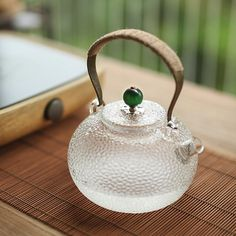 Brew your tea the traditional way with this beautiful and elegant clear glass teapot. It has a copper handle wrapped with hemp and a stunning green agate handle