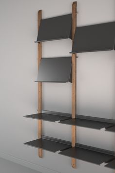 Unfinished reclaimed teak supports and bent sheet metal combine to create an adjustable shelving display unit. Hanging from a simple dowel on each end, shelves