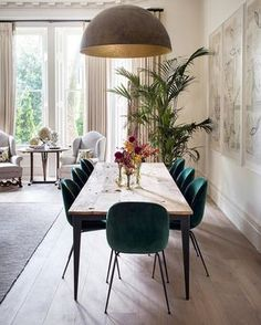 Modern dining room with green velvet chairs and large pendant light #diningroom