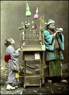 """""""The confections made from a paste are blown like glass into various shapes, and allowed to harden"""", quoted from the 1897 caption.  This studio shot is interesting: the poses are not standard, and the context they provide with their well-worn, everyday garments next to the beat-up portable """"Candy Store"""" makes this image valuable for capturing a seldom seen moment of a Child's life in old Japan."""