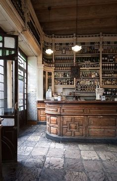 beautiful old cafè. wooden furniture, stone flooring  and shelves full of bottles. everything is antique here. antico bar e caffetteria d'epoca, con mobilia originale, scaffalature d'antiquariato piene di bottiglie e pavimento in pietra #bar #antiques #vintage   Concrete Living
