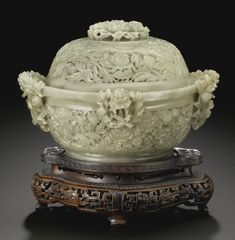 A CELADON JADE RETICULATED 'PEONY' CENSER AND COVER, QING DYNASTY, 18TH CENTURY the body on a slightly splayed circular foot, carved and intricately pierced with a meandering scroll of flowering peony blossoms, enveloped by curled leaves on winding stems, set with four clusters of peonies rising to the rim to form the handles, the domed cover with a circular and compressed openwork peony spray knop, the stone of pale celadon color with creamy-white and yellow inclusions and gray speckles.