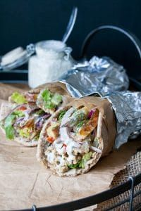 Two tempeh vegan greek gyros rolled up in pita bread and foil