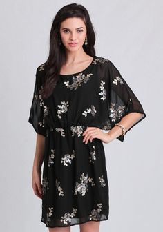 This black chiffon dress features a floral sequin pattern across the front in hues of gold and gray. Finished with sheer, dolman sleeves and an elastic waistband for the perfect fit, this darli...