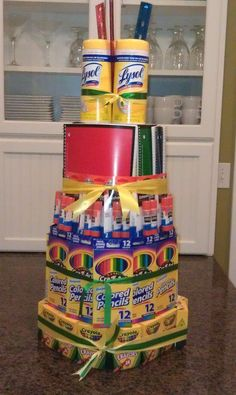 School supply cake. Bottom layer is 4 rolls of paper towels inside. middle layer is small wastebasket inside.