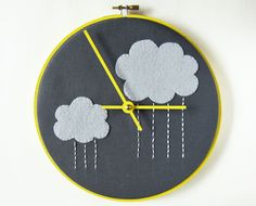 Felt clouds are appliquéd and rain drops are embroidered on charcoal cray cotton, mounted on a wooden base and finished in a bright yellow embroidery hoop. Best Embroidery Machine, Embroidery Patterns Free, Embroidery Designs, Diy Embroidery, Wall Clock Nursery, Fabric Wall Decor, Cactus Cross Stitch, Handmade Wall Clocks, Flower Chart