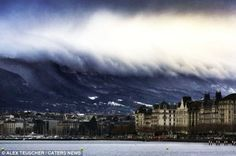 This is the dramatic moment a city in Switzerland looks like it is about to be engulfed by a giant tsunami - although the apparent tidal wave is actually just thick clouds rolling in over a mountain range.  December 16, 2012