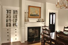 BM Halo walls, dark wood antiques, fireplace, built-in shelves, nautical art, bass and gold, glass fishing floats