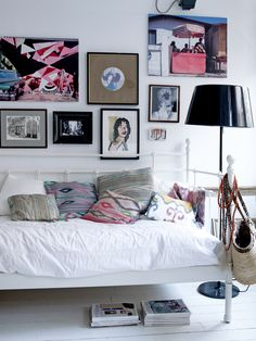 Bedroom with bed full of Ikat pillows #frames #black #white