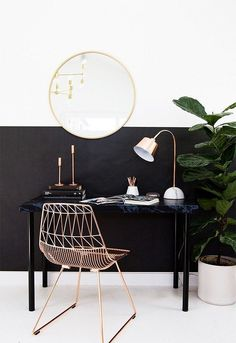 Modern workspace with a gold mirror, a rose gold metal chair, and a simple black desk