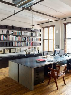 """Masculine New York Office That Feels like Home_Desks with stained-gray plywood topped with hot-rolled steel; melamine storage units are tucked beneath the structures to create a """"simple sculptural form."""" Beckstedt's desk exists within the open layout. """"This allows for a larger sense of community with the studio and for a constant ease of communication throughout the day."""""""