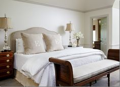 white bed linens w/ linen slipcovered headboard; box pleated and monogrammed linen shams; candlestick lamps