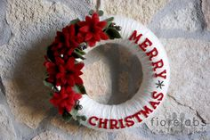 Wrap white yarn around a straw wreath then felt flowers and letters. Jingle bells are the perfect finish.