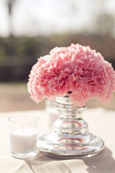 Pink Carnation bunched in a small pillar vase, accompanied by a votive.