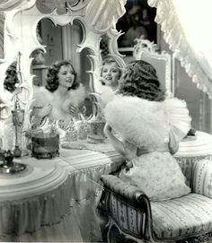 Janet Gaynor, she has a very tall 1920s perfume atomizer on her vanity!